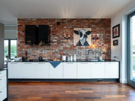 obraz krowy na ceglanej ścianie w kuchni